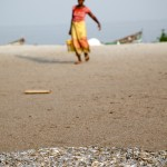 A woman carries water back from  the lake. In the foreground thousands of small fish called Dagaa dry in the sunshine.