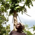 Mary Papa and a papaya tree. , Neema Women's Group, Kamasielo VillageMary Papa, Neema Women's Group, Kamasielo Village